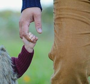 Niña agarrada de la mano de su padre, camino a la guardería.