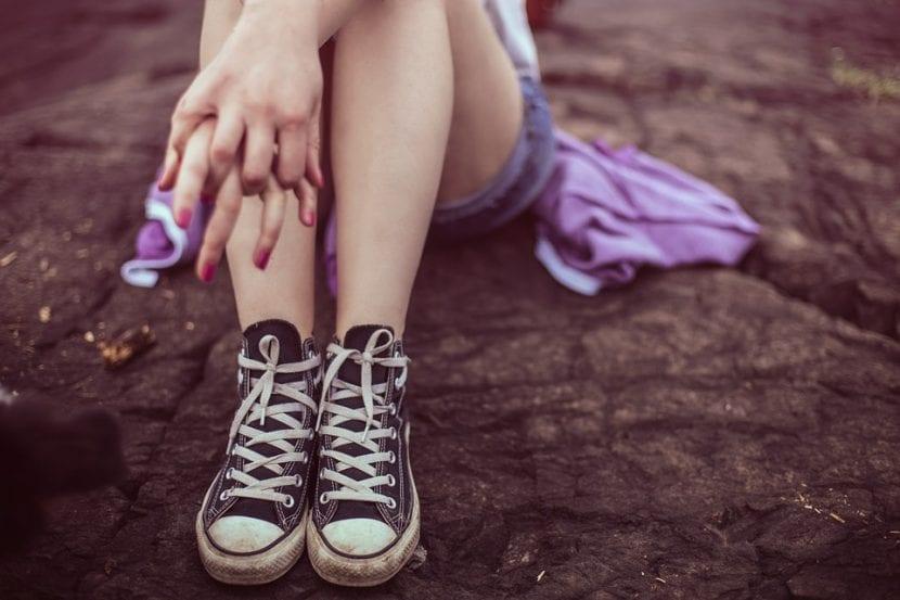 Joven pensativa con los dedos de las manos entrelazados permanece sentada y esperando.