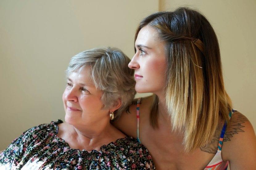 Madre e hija adultas se abrazan y miran juntas y en sintonía al mismo lugar.