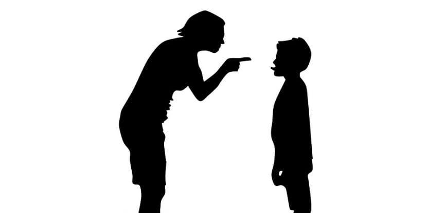 Madre señala a hijo enfadada, reprendiéndole por alguna acción indebida.