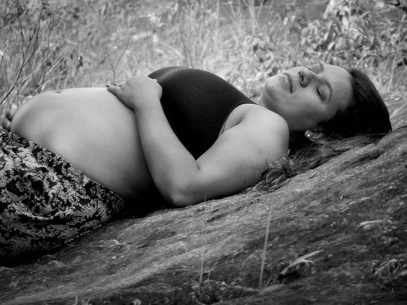 Embarazada tumbada entre la naturaleza buscando aliviar su malestar.