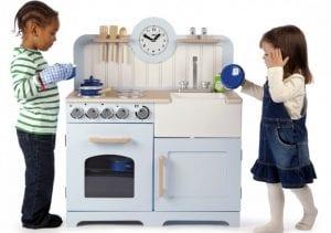 Niños jugando con una cocinita