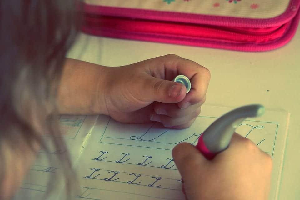Niña hace sola sus tareas de infantil.