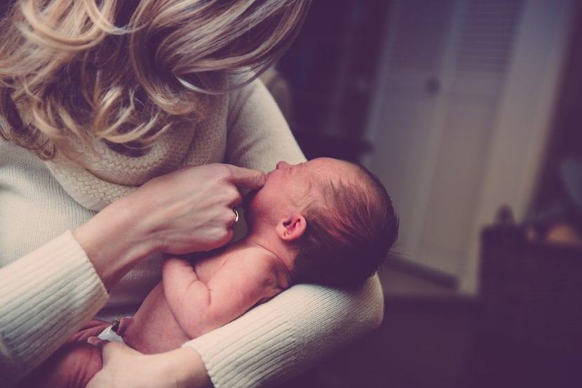 Madre acaricia a su bebé para consolar su llanto.
