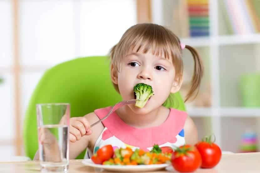 Niña comiendo verduras
