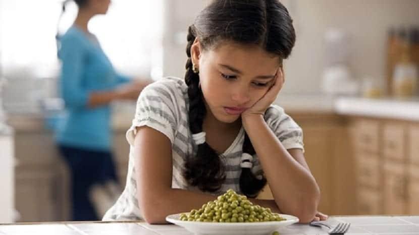 Niña frente a un plato de verduras