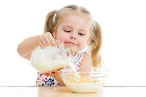Niña sirviendo leche