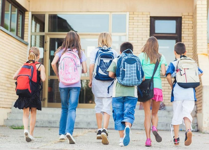 Niños con mochila escolar