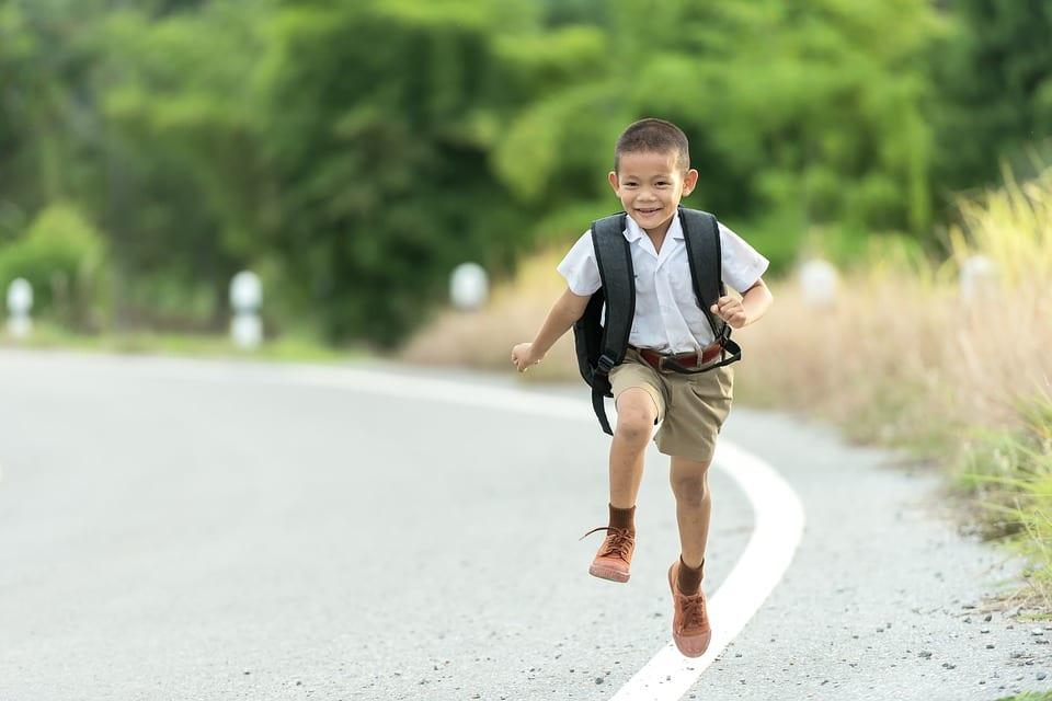 Niño que se dirige al colegio lleva mochila tradicional a la espalda.