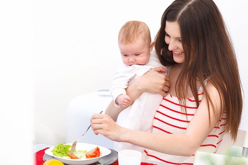 Madre comiendo con su bebé en brazos