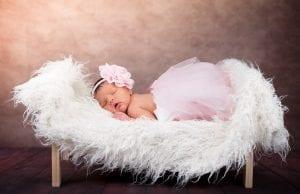 Bebé dormida sobre una cuna en sesión de fotos newborn