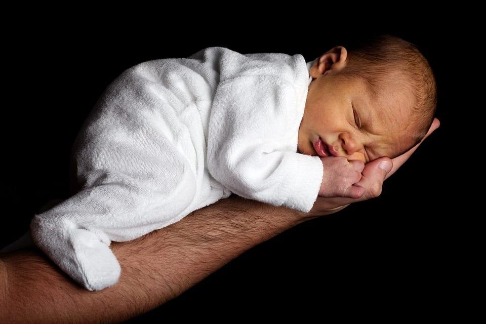 Padre sujeta a bebé en sesión de fotos