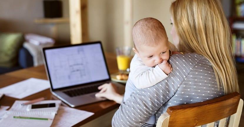 Madre estudiando con bebé en brazos
