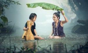 Madre e hija sonríen bajo la lluvia.