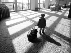 Niño arrastra su propia maleta con ruedas por el aeropuerto.