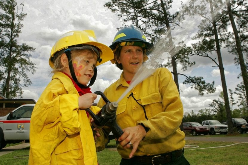 Mujer bombero enseña a niña su oficio.