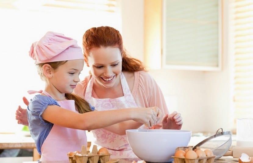 Una niña con su madre cocinando