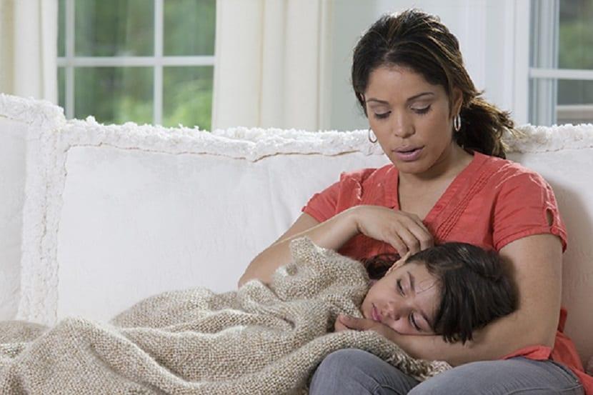 Niña enferma tumbada con su madre