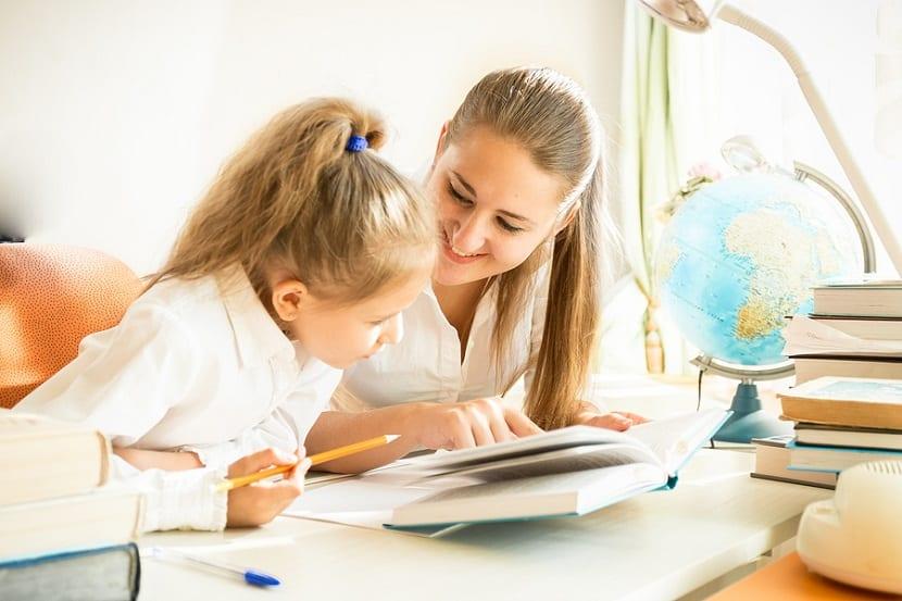 Niña estudiando con ayuda de su madre