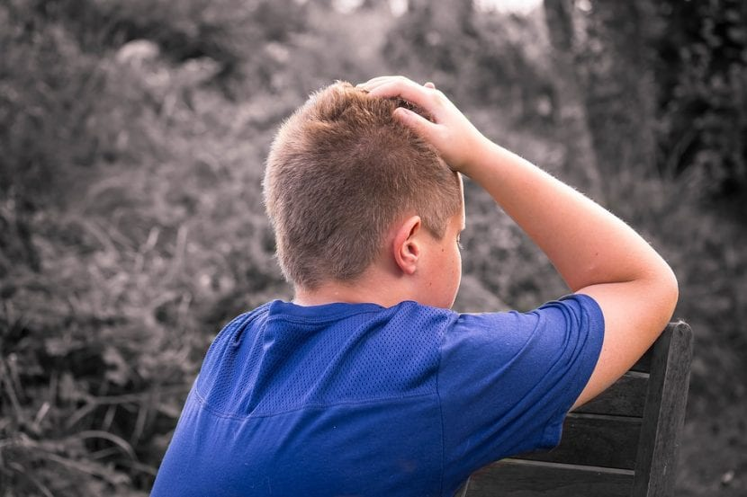 Niño agobiado ante síntomas que afectan a su habla se lleva las manos a la cabeza.