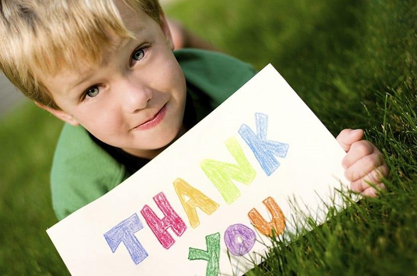 Niño con un cartel de gracias