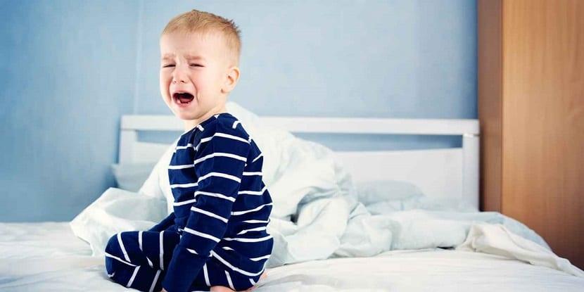 Niño pequeño llorando en su cama