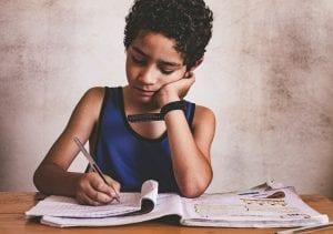 Niño sumido en la pobreza de su hogar completa un cuaderno de ejercicios.