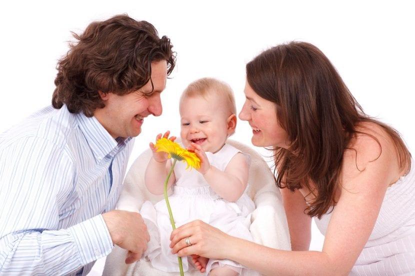 Padres sonríen viendo a su hijo sostener una flor.