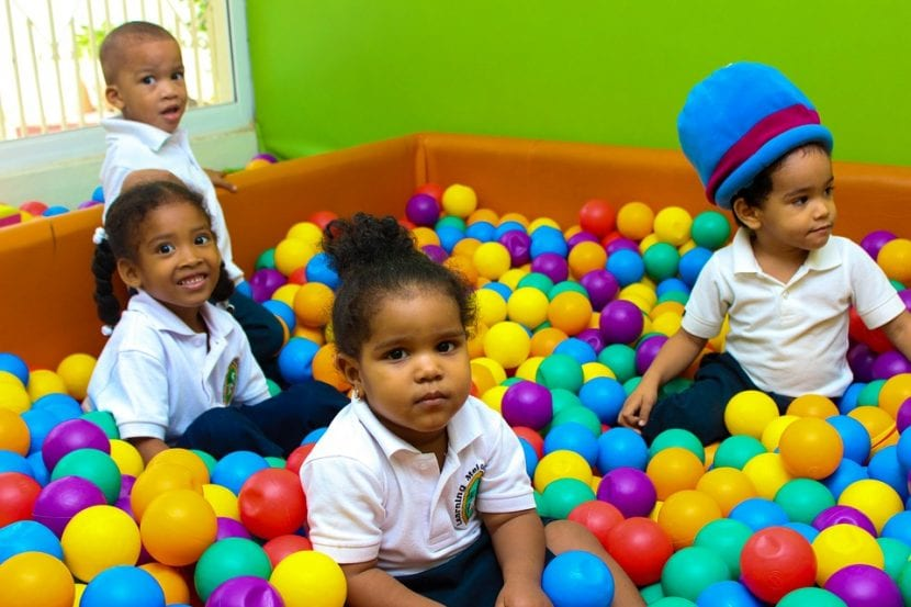 Niños juegan, con sus uniformes diferenciados, en el colegio.