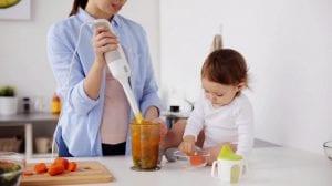 Madre cocinando con su bebé en la encimera