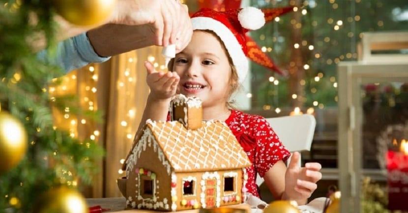 Niña haciendo una casita de jengibre de Navidad