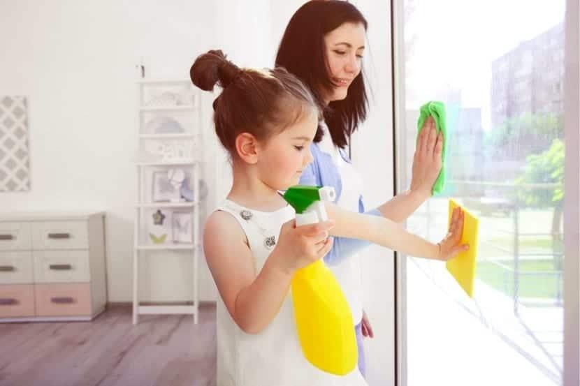 Niña limpiando los cristales