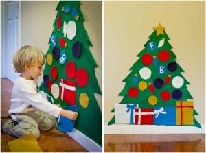 Niño jugando con un árbol de Navidad de fieltro