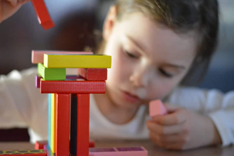 Niño se distrae jugando con diferentes fichas de colores.