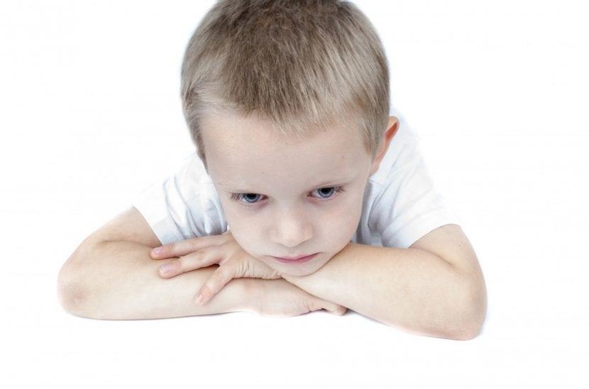 Niño pensativo y triste tras la regañina de su madre.