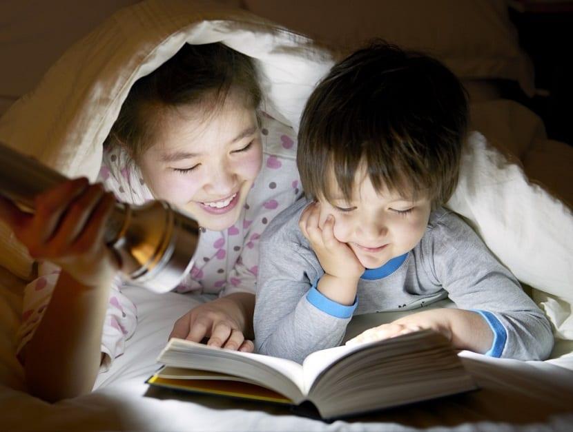 Niños leyendo un cuento en la oscuridad