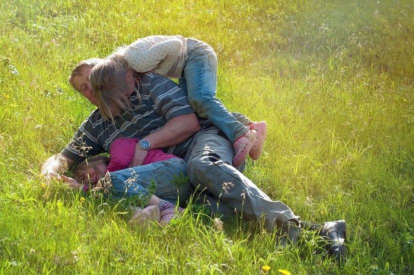Padre jugando con sus hijos al aire libre.