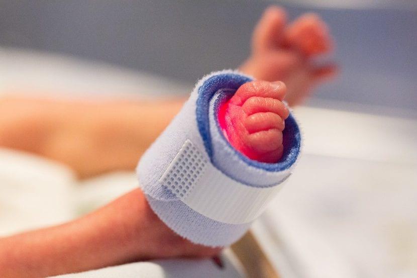 Bebé prematuro controlado con monitores en el hospital.