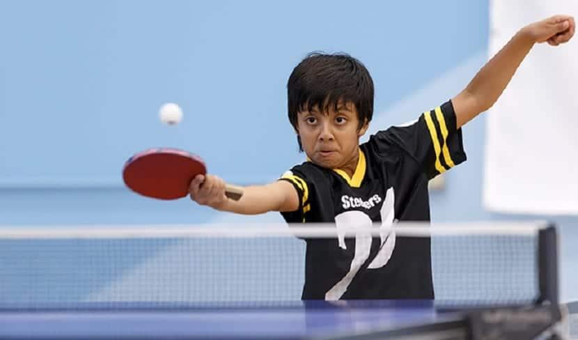 Niño con discapacidad jugando al tenis de mesa