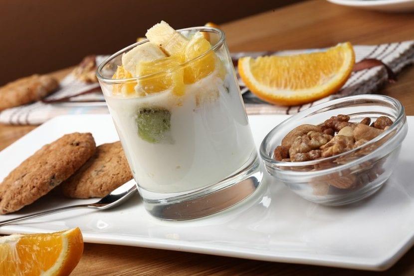 Completo desayuno compuesto por yogurt con frutas, cereales y galletas integrales.