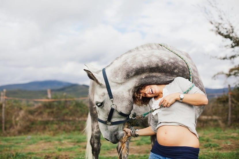 Mujer embarazada con un caballo