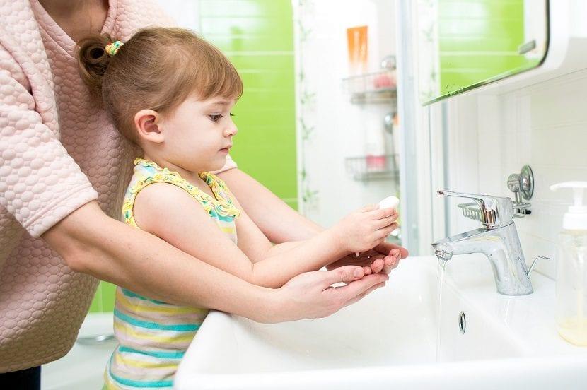 Madre enseñando a su hija a lavarse las manos