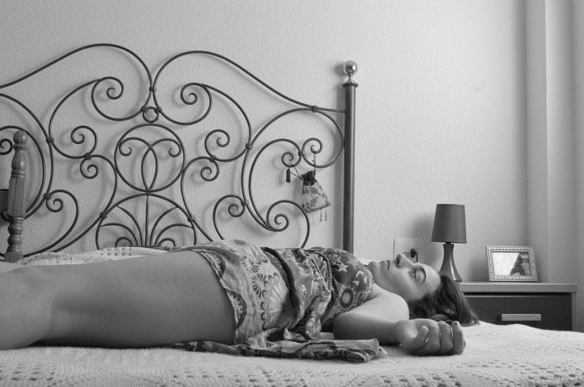 Madre con esclerosis múltiple se siente exhausta y reposa sobre la cama.