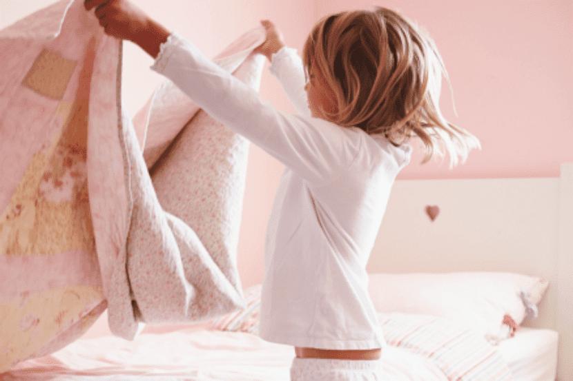 Niña haciendo su cama