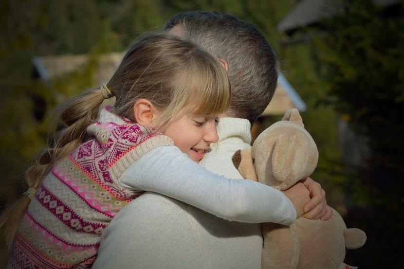 Niña se abraza fuerte y confiada a su padre, quien le enseña a respetar.