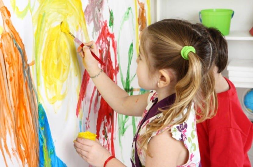 Niños pintando en un lienzo