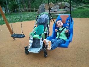 Niño con discapacidad se columpia.