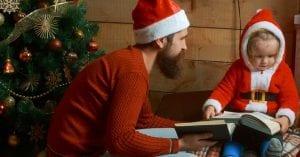 Padre joven lee un cuento de Navidad a su hija