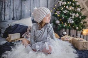 Niña desenvuelve regalos el día de navidad.