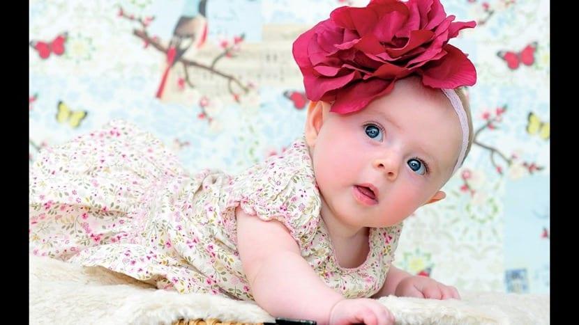 niña preciosa con flor en la cabeza